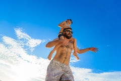 Eight years old boy sitting on dad`s shoulders. Both in swimming shorts and sunglasses, having fun on the beach. Bottom view. Blue sky and altocumulus clouds Stock Images