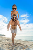 Eight years old boy sitting on dad`s shoulders. Both in swimming shorts and sunglasses, having fun on the beach. Bottom view Royalty Free Stock Photos