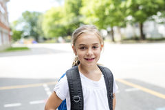 Eight years old school girl close to the schoolyards. A eight years old school girl close to the schoolyards stock photos
