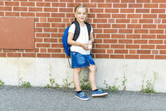 Eight years old school girl close to the schoolyards. A eight years old school girl close to the schoolyards stock photography