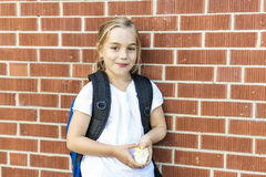 Eight years old school girl close to the schoolyards. A eight years old school girl close to the schoolyards royalty free stock image