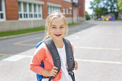 Eight years old school girl close to the schoolyards. A eight years old school girl close to the schoolyards royalty free stock photography