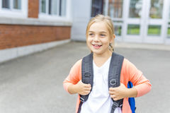 Eight years old school girl close to the schoolyards. A eight years old school girl close to the schoolyards stock photo
