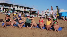 Eight young pretty women joyfully sit on sandy beach sunny summer day. Eight young pretty women wearing sunglasses, hats and swimming suits joyfully sit on stock video footage