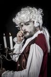 Eighteen era, gentleman rococo wig, candle. Gentleman rococo era wig, man dressed in vintage Royalty Free Stock Photo