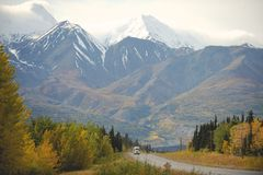 Eighteen-wheeler amongst Yukon mountains, Canada. Eighteen wheeler or truck driving on a highway through snow-capped mountains and autumn or fall colours on royalty free stock photos