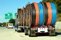 Eighteen Wheeler Loaded. Eighteen wheeler hauls a huge load of plastic pipe.  Colors are blue, orange, and black.  White van drives in front Stock Photo
