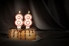 Eighty eight years anniversary. Birthday chocolate cake with white burning candles in the form of number Eighty eight. Dark background with black cloth stock images