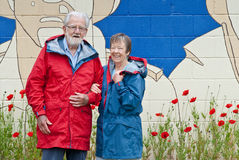 Eighty year old couple in red and blue raincoats. Near poppies stock photo