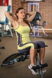 Eignung Junges schönes weißes Mädchen in einer gelben und grauen Sportklage tut Übungen auf Trainingsapparaten im Fitness-Club Lizenzfreies Stockbild