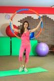 Eignung Junges schönes weißes Mädchen in einer rosa Sportklage tut körperliche Bewegungen mit einem Band in der Eignungsmitte lizenzfreies stockbild