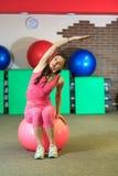 Eignung Junges schönes weißes Mädchen in einer rosa Sportklage tut körperliche Bewegungen mit einem rosa Sitzball in der Eignungs Stockfoto