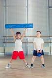 Eignung, Sport, Ausbildungslebensstilkonzept - Kinder in den Turnhallengewichten und mit Schaumrolle Stockfoto