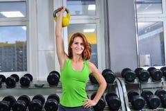 Eignung, Sport, Lebensstil ausübend - athletische Frau des Mittelalters, die oben muscules mit Dummkopf pumpt lizenzfreie stockbilder