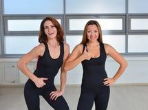 Eignung, Sport, Lebensstil ausübend - zwei glückliche junge Frauen, die zusammen in einer Turnhalle nah stehen und sich Daumen ze lizenzfreie stockfotografie