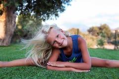Eignung, Sport, Trainieren, Ausdehnen und Leutekonzept - lächelndes blondes Mädchen, das Spalten auf dem Gras tut Lizenzfreie Stockfotografie