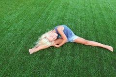 Eignung, Sport, Trainieren, Ausdehnen und Leutekonzept - lächelndes blondes Mädchen, das Spalten auf dem Gras tut Lizenzfreies Stockbild