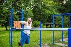 Eignung, Sport, trainierend, Ausbildungs- und Lebensstilkonzept Der junge Mann, der Trizeps tut, tauchen auf Barren, draußen ein Lizenzfreies Stockbild