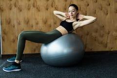 Eignung, Sport, Training, Turnhalle und Lebensstilkonzept - junge Frau, die Übung auf Eignungsball tut Lizenzfreies Stockbild