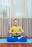Eignung Sport-, Trainings- und Lebensstilkonzept - Kind, das Übungen auf Matte im Haus tut Lizenzfreie Stockfotos