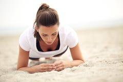 Eignungs-Frau auf dem Strand, der Kern-Übungen tut Stockfotografie