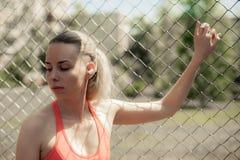 Eignungs-Frauen-hörende Musik in den drahtlosen Kopfhörern, Trainings-Übungen auf Straße tuend Sportart Bluetooth-Kopfhörer Lizenzfreies Stockbild