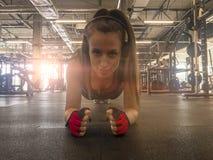 Eignungs-Frauen-h?rende Musik in den drahtlosen Kopfh?rern Handeln von Trainingsübungen in der Turnhalle Schönes athletisches gee lizenzfreie stockfotos