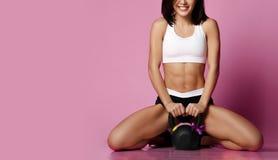 Eignungs-Mädchen, das mit dem glücklichen Lächeln des großen Gewichtsdummkopfs auf Rosa ausarbeitet Sport arbeitet Konzept für Fr lizenzfreie stockfotografie