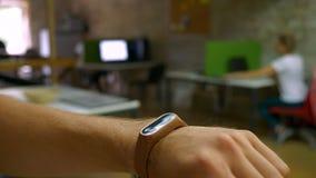 Eignungsarmband auf der Hand des Mannes es anschaltend und Einstellungen, Büro ändernd Innen stock video