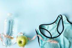 Eignungsausrüstung mit Taillenmaß, BH und dem grünen Apfel auf blauem Hintergrund Notizblockraum für Texteingabe auf Gesundheitsw stockbilder