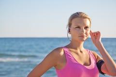 Eignungsfrau auf dem Strand in den Kopfhörern Stockfotos