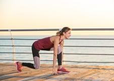 Eignungsfrau in der Position bereit, auf Pier zu laufen lizenzfreie stockfotografie