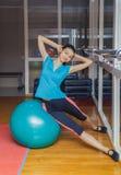 Eignungsfrau in der Turnhalle, die auf pilates Ball stillsteht Junge Frau, die Übung auf Eignungsball tut Mädchen mit Eignungsbal Stockbild