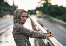 Eignungsfrau, die Abstand in der regnerischen Stadt untersucht Stockfotografie