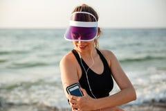 Eignungsfrau, die auf dem Strand hört Musik mit Telefon stillsteht Stockfotos