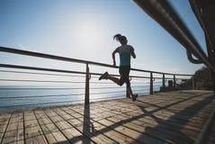 Eignungsfrau, die auf Küste läuft Stockfotos