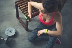 Eignungsfrau, die in der Dachbodenturnhalle mit Handy sitzt stockbild