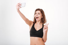 Eignungsfrau, die Friedenszeichen zeigt und selfie mit Smartphone nimmt Stockfotografie