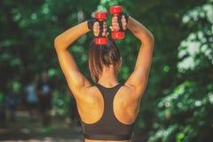 Eignungsfrau, die Gewichte im Waldmorgengymnastikkonzept hält lizenzfreies stockfoto