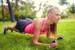 Eignungsfrau, die im Park, auf Gras ausdehnt und ausarbeitet Stockfotografie