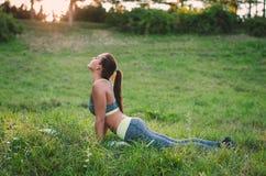 Eignungsfrau, die im Wald nahe einem Baum stillsteht nach einem w sitzt Stockfoto