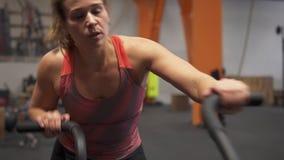 Eignungsfrau, die Luftfahrradübung in der Turnhalle tut stock footage