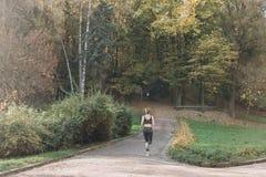Eignungsfrau, die in Morgenpark läuft Athletische Frau, die auf die Wiese mit grünem Gras im Park ausdehnt lizenzfreie stockfotografie