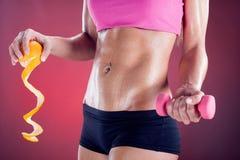 Eignungsfrau, die Orange und Gewichte, gesundes Lebenkonzept hält Lizenzfreie Stockbilder