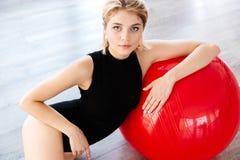 Eignungsfrau im Trikotanzug, der auf rotem fitball sitzt und sich lehnt Stockfotos