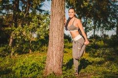 Eignungsfrau im Wald, die das Ausdehnen nach einem Training tut paßsitz Lizenzfreie Stockbilder