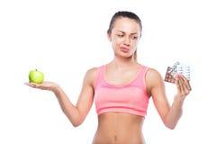 Eignungsfrau mit Pillen in einer Hand und grüner Apfel in anderen Stockfotos
