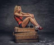Eignungsfrau sitzt auf einer Holzkiste auf grauem Hintergrund Lizenzfreie Stockbilder