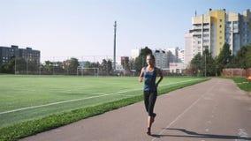Eignungsfrauenläufer, der auf Stadionsbahn läuft stock footage