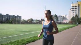 Eignungsfrauenläufer, der auf Stadionsbahn läuft stock video footage